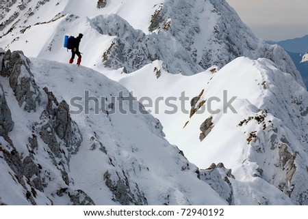 Lonely alpinist on a mountain ridge