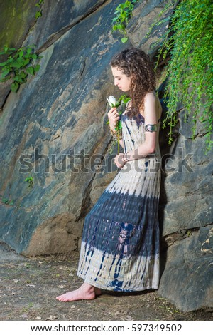 2a409eb65bf Lonely American teenager girl with curly hair, wearing patterned long  dress, bracelet, barefoot