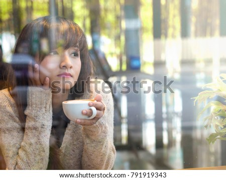 Lonely Asian woman drinking hot coffee in glasses house cafe looking out side from window waiting for someone