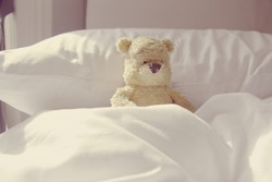 Lonely bear is  laying in bed. Idea for sick or lazy in bed in bedroom.