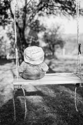 Lonely Bear Toy swinging outdoors in empty Park. Teddy Bear waiting on swing in playground. Vertical black and white photo