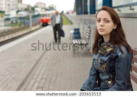 Lonely beautiful girl, with a deep look and a sad facial expression, sitting on a bench while waiting in an urban railway station