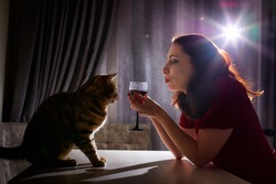 Lonely beautiful middle aged woman alone in the dark kitchen drinking red wine in the evening or night with her cat. Concept of loneliness. Concept of pleasure. Drinking and depression