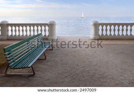 Lonely bench on a background of sea and a lonely sail