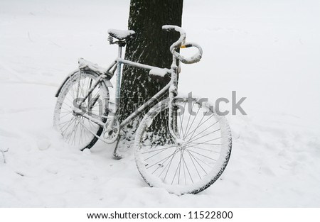 Lonely bicycle covered by snow near tree.