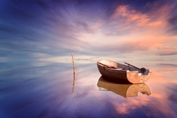 Lonely boat and amazing sunset at the sea