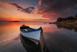 Lonely boat at sunset. Calm and beautiful sunrise near Madeira, Portugal. Amazing landscape with wooden boat against the sun, majestic clouds in the sky, old  boat on the coast at mountain background.