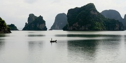 Lonely boat drifts through calm Halong Bay islands, Vietnam,Asia