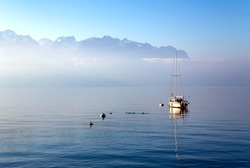 Lonely boat on Lake Leman or Lake of Geneva with morning mist over the water surface. At the background are the snow-covered Alps in Montreux, Switzerland