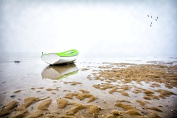 Lonely boat on the beach a foggy day