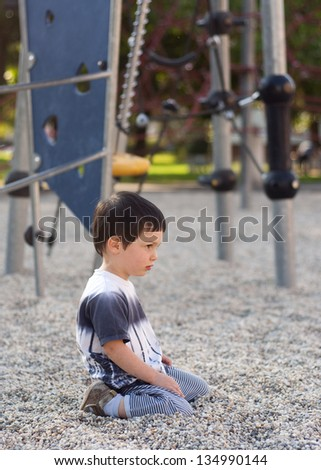 Lonely bored child sitting on ground in playground.
