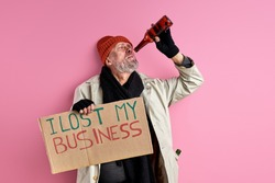 lonely bum man lost his job, business due to covid-19, coronavirus. homeless male stand drinking alcohol, isolated pink background