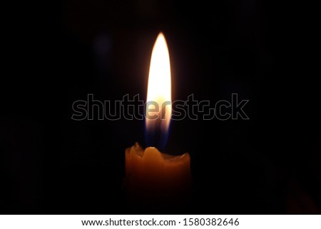 Lonely burning candle in the dark, on a dark background