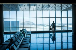 Lonely business man travel and wait at the airport gate - concept of delay and cancel filght problem and passenger rights - people move life and transport station