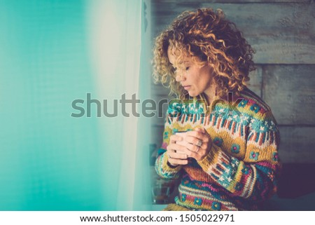 Lonely cacuasian adult lady at home - people relaxing and taking his own time lost in own thoughts - portrait of beautiful middle age woman with cup of coffee