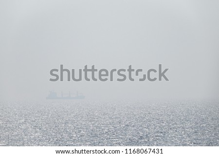 Lonely cargo ship. Fog and mist in infinite, endless ocean. Concept for lost at sea. Background with copy space for text.