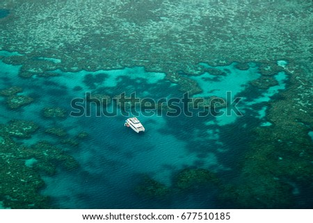 Lonely catamaran in the Great Barrier Reef as seen on the outer reef away from the Whitsunday Islands and Airlie Beach. #677510185