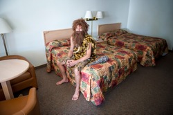 Lonely caveman traveler sitting indoors on the edge of double bed in a dingy motel room