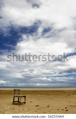 Lonely chair on beach with dramatic clouds.
