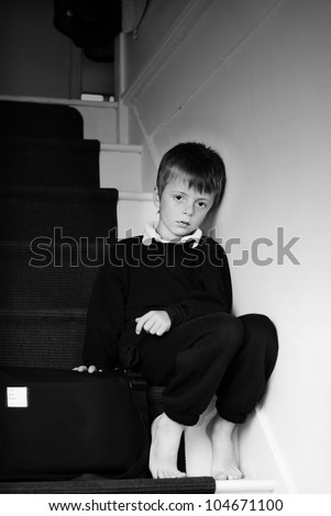 Lonely child sitting on the stairs.