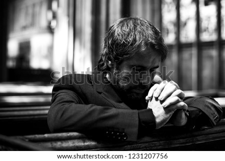 Lonely Christian man praying in the church #1231207756