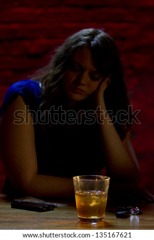 Lonely, depressed girl at a bar with drink