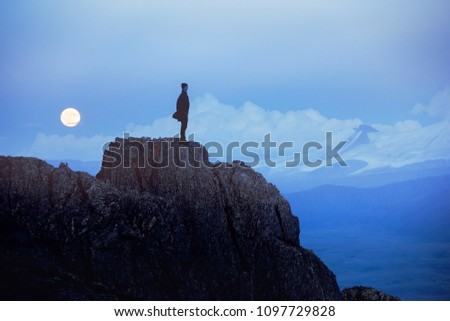 Lonely depressed man at evening time stands on cliff or big rock against mountains and moon