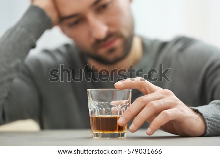 Lonely depressed man drinking whisky at home, closeup