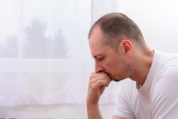 Lonely depressed man near window at home. Unhappy male Isolated on white background. Miserable Caucasian middle aged man at home. Staying at home can help stop coronavirus spreading concept.