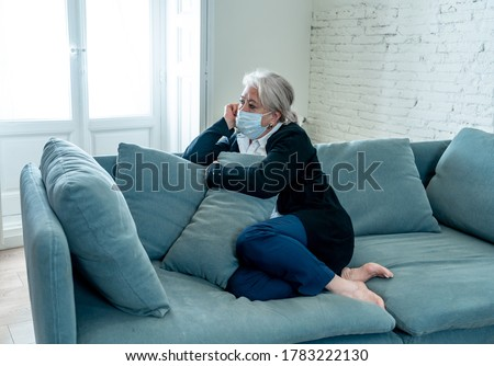 Lonely depressed senior widow woman with protective mask crying on couch isolated at home, sad and worried missing husband and family in COVID-19 death, lockdown, social distancing and Mental health.