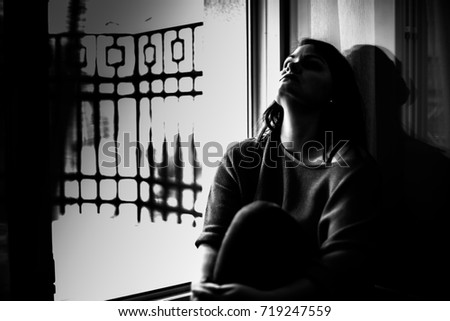 Lonely depressed woman sitting on the floor near balcony, looking at rain, feel tired, sad and unhappy. Black and white photo