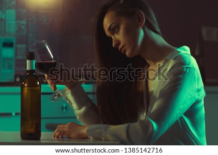 Lonely, divorced beautiful young woman with alcoholic beverage is drinking alone in evening at home. Female alcoholism and alcohol addiction. Life difficulties and problems #1385142716