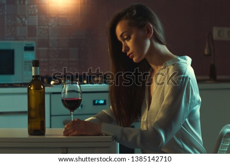Lonely, divorced beautiful young woman with alcoholic drinks is drinking alone in evening at home. Female alcoholism and alcohol addiction. Life difficulties and problems #1385142710