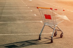Lonely empty grocery cart in an empty parking lot near a supermarket at sunset. The concept of food shortages, deficit, lack of people, quarantine