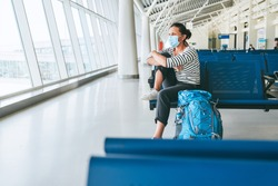 Lonely female solo traveler with backpack sitting in the empty airport passenger transfer hall in protective face mask and looking out large windows. Traveling in worldwide pandemic time concept image