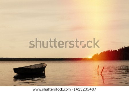 lonely fishing boat docked in calm lake. wooden fishing boat in a still lake water. image of wooden fishing boat moored on the shore. space for text. Toksovo, lake Kavgolovo