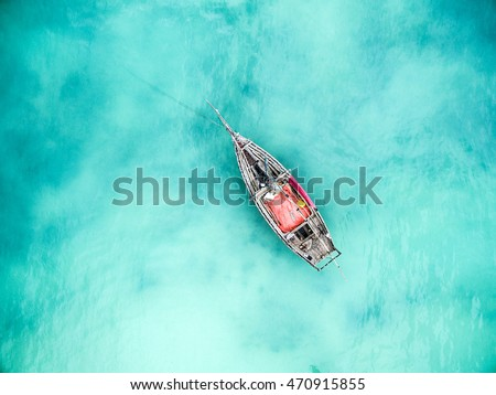 lonely fishing boat in clean turquoise ocean, aerial photo, top view