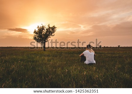 Lonely girl and lonely tree.