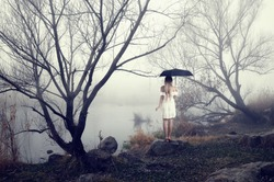 Lonely girl in a white dress with an umbrella standing among the trees in the mist near the river. Autumn landscape. Rain.