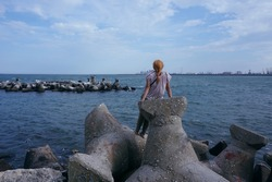Lonely girl looking at the sea, thinking about the future, solo traveler