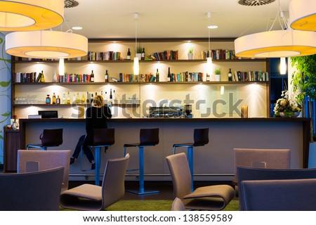 lonely girl sits alone at modern illuminated hotel bar
