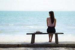 Lonely girl sitting On the natural ocean background. blurred Alone by the sea