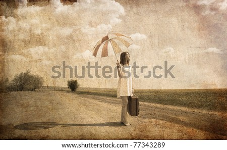 Lonely girl with suitcase and umbrella at country road. Photo in old image style.