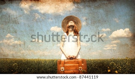 Lonely girl with suitcase at country.