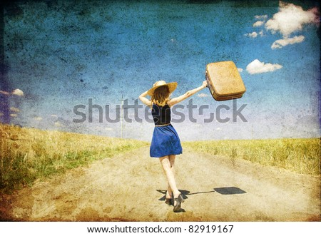 Lonely girl with suitcase at country road. Photo in old color image style.