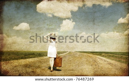 Photo of Lonely girl with suitcase at country road. Photo in old image style.