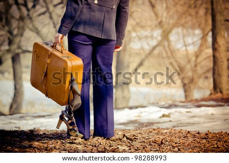 Photo of Lonely girl with suitcase walking outdoor