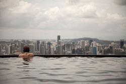 lonely girl with tattoo in a swimming pool looking over the city. In Singapore, in hotel Marina Bay Sands