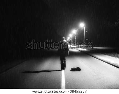 Lonely guy in darkness on the middle of road