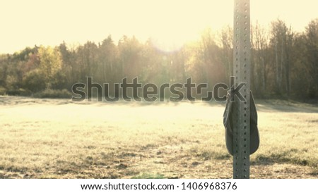 Lonely hat hanging from pole in a tranquil natural landscape. Solitude image. #1406968376